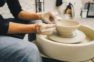Woman making pottery in Arts & Crafts community near cabins in Gatlinburg